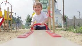 Niño del muchacho que balancea hacia arriba y hacia abajo en un oscilación del patio almacen de video