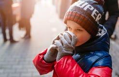 Niño del muchacho que bebe el cacao caliente de la taza de papel Foto de archivo libre de regalías