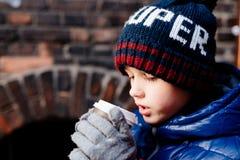 Niño del muchacho que bebe el cacao caliente de la taza de papel Imágenes de archivo libres de regalías