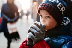 Niño del muchacho que bebe el cacao caliente de la taza de papel Fotografía de archivo