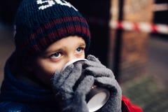 Niño del muchacho que bebe el cacao caliente de la taza de papel Imagen de archivo libre de regalías