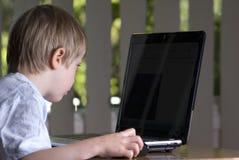 Niño del muchacho que mira la pantalla de la computadora portátil Fotos de archivo libres de regalías