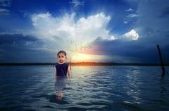 Niño del muchacho que se coloca en agua durante salida del sol de la puesta del sol en waterscape Imágenes de archivo libres de regalías