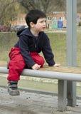 Niño en la parada de autobús imagenes de archivo