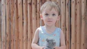 Niño del muchacho que sostiene un juguete suave y que sonríe en sus manos almacen de video