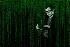 Niño del negocio con adentro un ordenador portátil del traje en estilo de la matriz pirata informático en fondo techno-digital Imagen de archivo