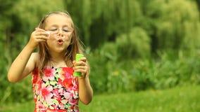 Niño del niño de la muchacha burbujas de un jabón que soplan al aire libre almacen de video
