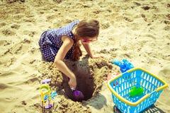 Niño del niño de la niña con el juguete que se divierte en la playa Foto de archivo