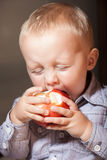 Niño del niño del niño pequeño que come la fruta de la manzana en casa Fotos de archivo