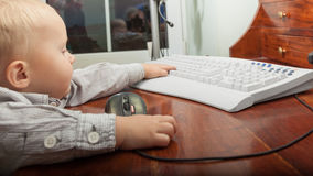 Niño del niño del niño pequeño que juega en el ordenador Imágenes de archivo libres de regalías