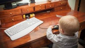 Niño del niño del niño pequeño que juega en el ordenador Fotografía de archivo libre de regalías
