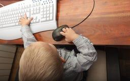 Niño del niño del niño pequeño que juega en el ordenador Imagenes de archivo