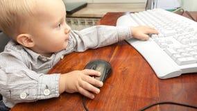Niño del niño del niño pequeño que juega en el ordenador Foto de archivo