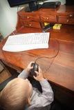 Niño del niño del niño pequeño que juega en el ordenador Imagen de archivo libre de regalías