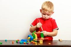 Niño del niño pequeño que juega con los juguetes de las unidades de creación interiores Foto de archivo