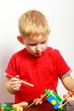 Niño del niño pequeño que juega con los juguetes de las unidades de creación interiores Imagen de archivo libre de regalías
