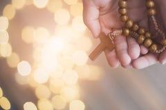 Niño del niño pequeño que ruega y que sostiene el rosario de madera foto de archivo