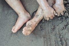 Niño del niño que juega en la arena de la playa con la protección solar en cierre encima opinión superior de los fondos del día d Foto de archivo libre de regalías