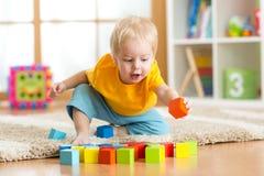 Niño del niño que juega los juguetes de madera en casa Fotografía de archivo libre de regalías