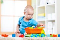 Niño del niño que juega los juguetes de madera en casa Fotos de archivo libres de regalías