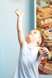 Niño del pequeño niño que alcanza para arriba en casa Fotografía de archivo