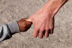 Niño del refugiado a mano de un ayudante Imagen de archivo libre de regalías