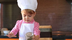 Niño del retrato de Clouse-up el pequeño en traje del cocinero ayuda a su madre a cocinar en la cocina almacen de metraje de vídeo
