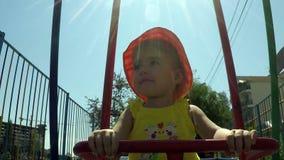 Niño del retrato de Clouse-up pequeño en un oscilación en un fondo del sol en un cielo azul almacen de video