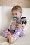 Niño del retrato de Clouse-up pequeño que se sienta en la cama en el cuarto que abraza un lémur relleno del juguete Fotos de archivo libres de regalías