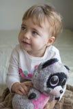 Niño del retrato de Clouse-up pequeño que se sienta en la cama en el cuarto que abraza un lémur relleno del juguete Imagen de archivo