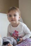 Niño del retrato de Clouse-up pequeño que se sienta en la cama en el cuarto que abraza un lémur relleno del juguete que mira la c Imágenes de archivo libres de regalías