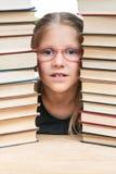Niño del retrato entre las pilas de libros Fotos de archivo