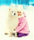 Niño del retrato que abraza el invierno blanco del perro del samoyedo Imagen de archivo libre de regalías