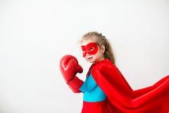 Niño del super héroe en los guantes de boxeo aislados en el fondo blanco imagen de archivo libre de regalías