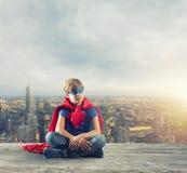 Niño del super héroe que sienta en una pared que sueños imagen de archivo libre de regalías