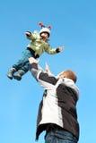 Niño del vuelo sobre el cielo, manos del padre. Fotos de archivo