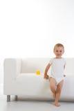 Niño delante del sofá/del sofá Imagen de archivo