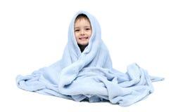 Niño después del baño que se sienta en cama Foto de archivo