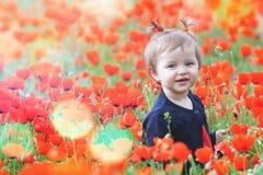 Niño divertido al aire libre en el campo de la amapola Foto de archivo libre de regalías