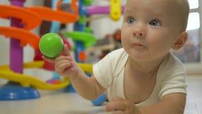 Niño divertido alegre con las bolas coloreadas en las manos que intentan arrastrarse cerca para arriba almacen de video