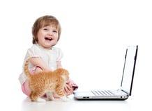 Niño divertido con el gatito y la computadora portátil foto de archivo libre de regalías
