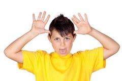 Niño divertido con la camiseta amarilla que imita Imágenes de archivo libres de regalías