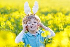 Niño divertido de 3 años con los oídos del conejito de pascua, celebrando Pascua Fotografía de archivo