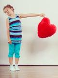 Niño divertido de la niña con la almohada roja de la forma del corazón Imagen de archivo libre de regalías