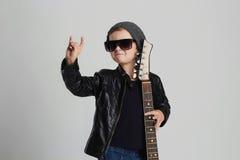 Niño divertido de la roca con la guitarra Niño pequeño en gafas de sol Fotos de archivo libres de regalías