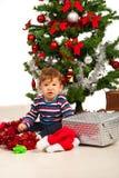 Niño divertido debajo del árbol de navidad Fotografía de archivo