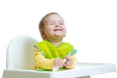 Niño divertido del bebé que se sienta en highchair con una cuchara Fotografía de archivo libre de regalías