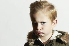 Niño divertido en abrigo de invierno Little Boy hairstyle Fotos de archivo libres de regalías