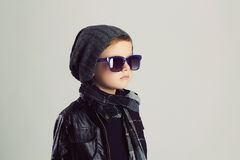 Niño divertido en bufanda y sombrero Niño pequeño de moda en gafas de sol Fotografía de archivo libre de regalías