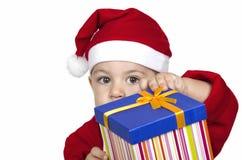 Niño divertido en el sombrero rojo de Papá Noel que sostiene el regalo de la Navidad disponible. Fotos de archivo libres de regalías